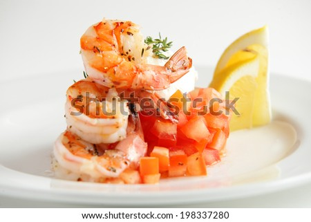 fresh and tasty shrimps with lemon and tomato on white dish - stock photo