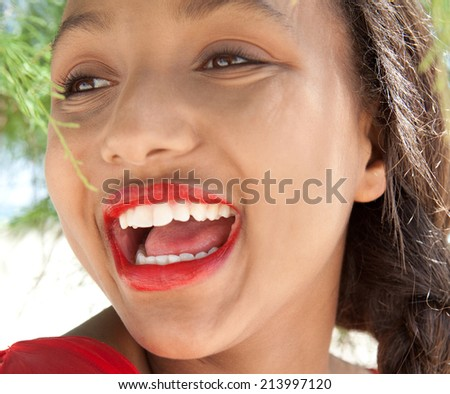Fresh and vibrant beauty portrait of a laughing african american teenager girl with a fun expression and wearing red lipstick and enjoying a summer holiday. Beauty and healthy lifestyle, outdoors. - stock photo