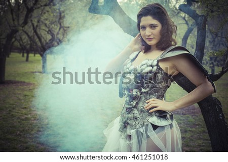 Fresh, angel brunette woman with iron armor and black wings in a forest. romantic scene