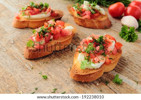Fresh antipasto called bruschetta with tomato, garlic, cheese and herbs on a wooden table - stock photo