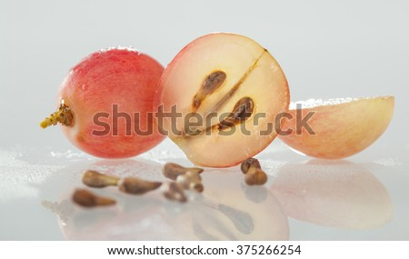 Fresh appetizing grapes and grape seeds on gray background with reflection - stock photo