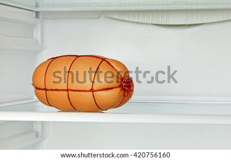 Fresh appetizing sausage on refrigerator shelf taken closeup. - stock photo