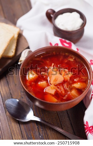 Fresh appetizing vegetable soup borscht with potato, carrot, onion, tomato, beetroot in  bowl on table. Selective focus. - stock photo