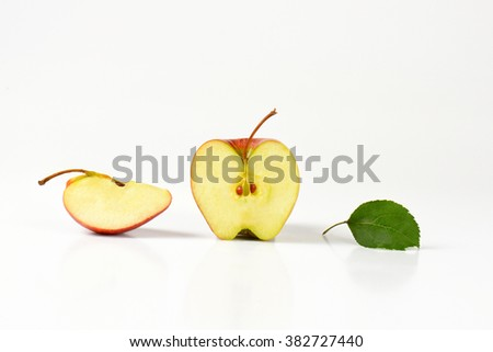 fresh apple half and quarter on white background - stock photo