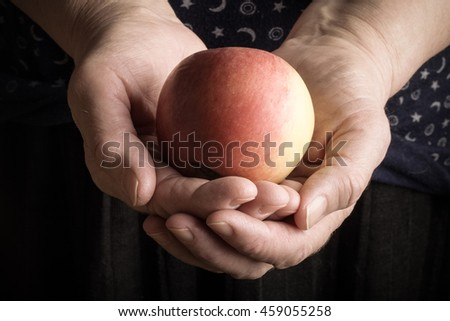 Fresh apple in the hands of an elderly woman. Toned.