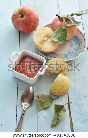 fresh apple jam and apples on blue background