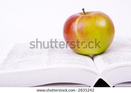 fresh apple on a book - stock photo