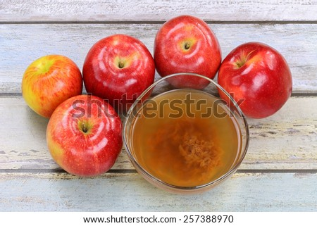 Fresh apples and a bowl of raw and unfiltered organic apple cider vinegar with mother enzymes - stock photo