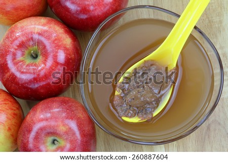 Fresh apples and a bowl of raw and unfiltered organic apple cider vinegar with mother enzymes on a wooden background - stock photo