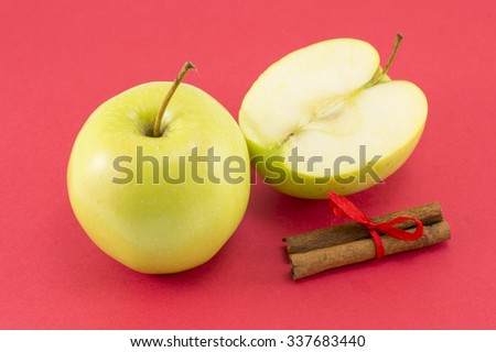 Fresh apples and cinnamon sticks with a ribbon on red background