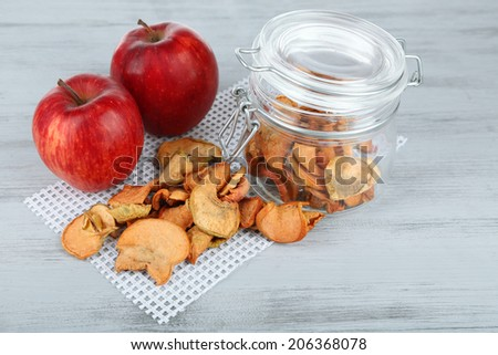 Fresh apples and dried apples in glass jar, on color wooden background - stock photo