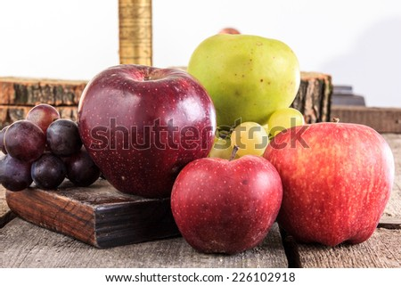 Fresh apples and grapes on wooden background in domestic composition - stock photo