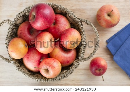 Fresh apples in a basket on a table from directly above. - stock photo