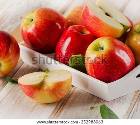 Fresh apples  in white box on  wooden table. Selective focus