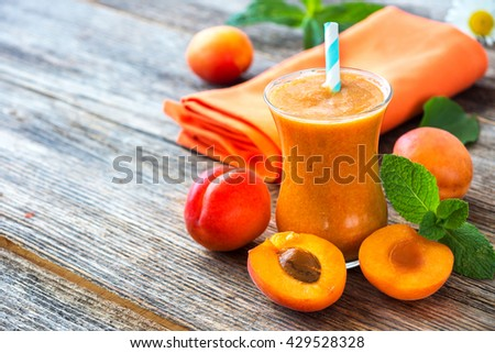 Fresh apricot smoothie and apricots on wooden  background