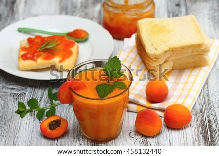 Fresh apricot  smoothie in glass, apricot jam on toast and  apricots around