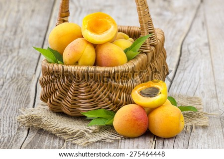 fresh apricots in a basket on wooden background - stock photo