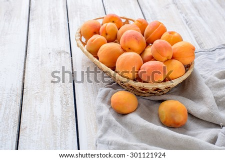 Fresh apricots in a wicker basket on linen napkin on wooden table/A basket of fresh apricots on vintage wooden table  - stock photo
