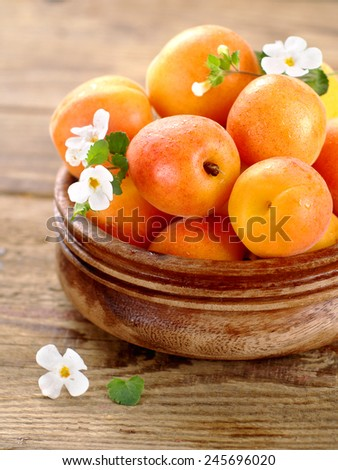 Fresh apricots in wooden bowl, selective focus - stock photo
