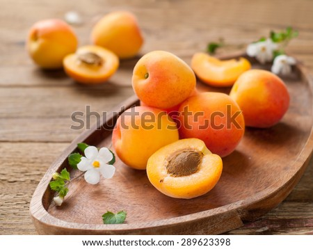 Fresh apricots on wooden plate, selective focus