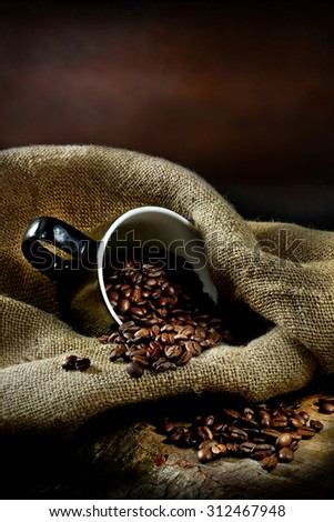 Fresh aromatic coffee beans against hessian fabric set in a rustic setting with creative lighting. Concept image for breakfast or a coffee house menu cover image. Copy space. - stock photo