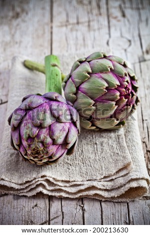 fresh artichokes on rustic wooden background - stock photo