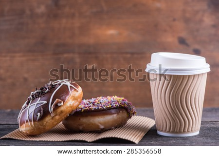 fresh artisan donuts and take away coffee, wooden background with copy space - stock photo