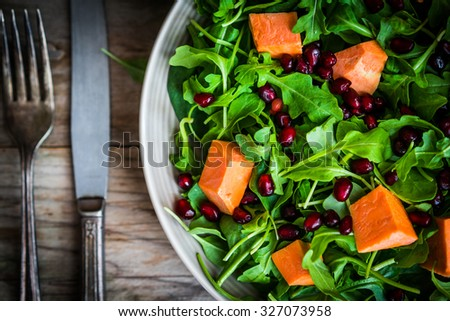 Fresh arugula and spinach salad with pumpkin on rustic background