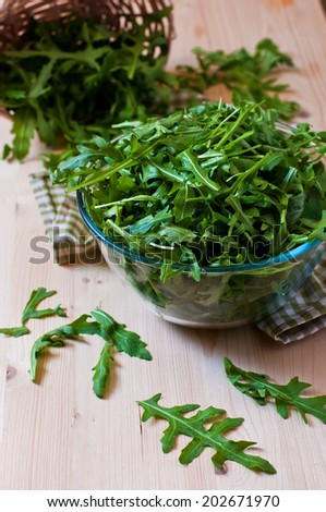Fresh arugula in a glass plate on the wood  table - stock photo