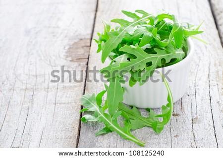 Fresh arugula leafs in bowl on table - stock photo