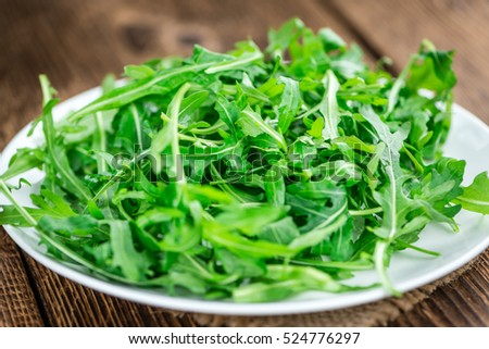 Fresh Arugula on an old wooden table as detailed close-up shot