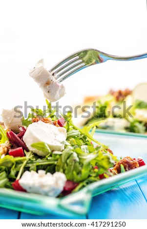 fresh arugula salad with beetroot, goat cheese, bread slices and walnuts with metal fork in hand, product photography for restaurant or healthy lifestyle - stock photo