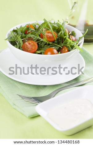 Fresh arugula salad with cherry tomatoes in a white bowl