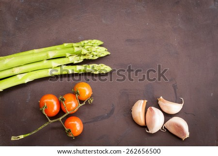 Fresh asparagus, garlic and tomatoes on black table background. Vegetable food. - stock photo