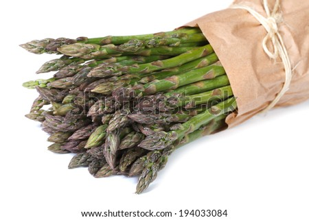 Fresh asparagus shoots in paper packing isolated on a white background close up horizontal   - stock photo