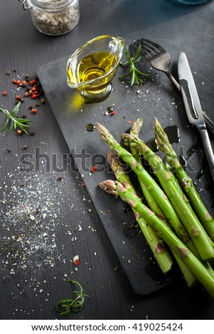 Fresh asparagus with olive oil and seasonings and ingredients for cooking on dark background. Shallow focus.  - stock photo