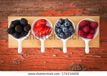 Fresh assorted berries on a grungy wooden counter displayed in small ceramic ramekins including blackberries, blueberries, strawberries and raspberries for a healthy snack or appetizer - stock photo