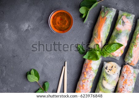 Fresh assorted spring rolls set background. Handmade asian/Chinese spring rolls, sauce, chopsticks. Rustic concrete background. Spring rolls with shrimps, vegetables, fruits. Space for text. Top view