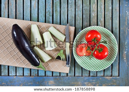 Fresh aubergines and tomatoes  for slicing on a wooden worktop - stock photo