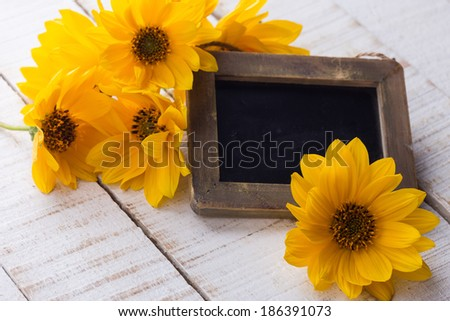 Fresh autumn flowers with empty blackboard on white wooden background. Copy space.Selective focus.
