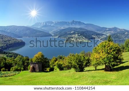fresh autumn landscape with Carpathian mountain and lake, Romania - stock photo