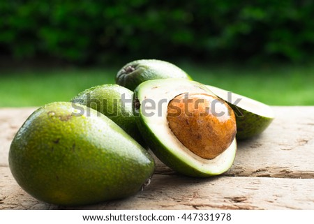 fresh avocado and slices avocado on old wooden background Selected focus - stock photo