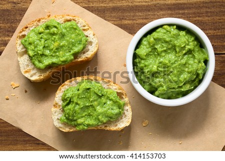 Fresh avocado cream or guacamole on baguette slices, photographed overhead with natural light (Selective Focus, Focus on the top of the avocado cream in the bowl and on the bread slices)