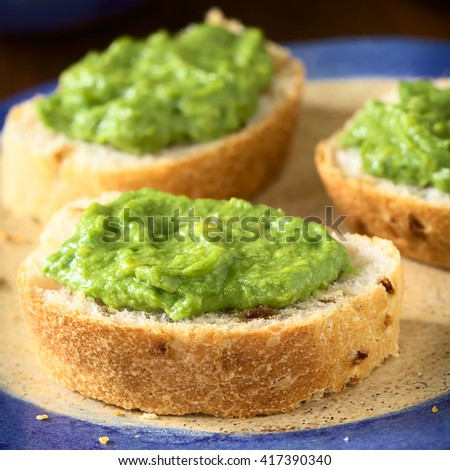 Fresh avocado cream or guacamole on onion bread slices, photographed with natural light (Selective Focus, Focus on the front of the avocado cream on the first bread)