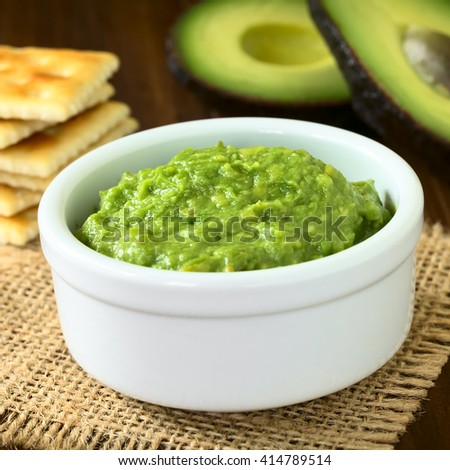 Fresh avocado cream or guacamole with soda crackers and half avocados in the back, photographed with natural light (Selective Focus, Focus in the middle of the avocado cream)