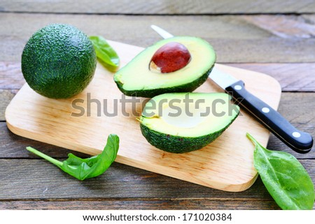 fresh avocado on a kitchen board, food closeup - stock photo