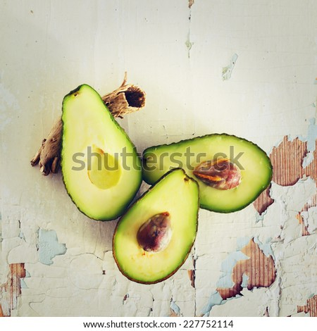 Fresh avocado on wooden rusty background. Instagram color effect. - stock photo