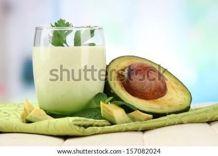 Fresh avocado smoothie on bright background - stock photo