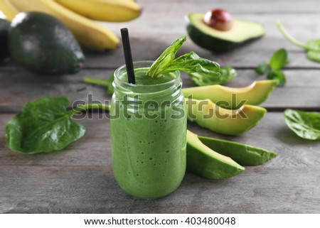 Fresh avocado smoothie with slices on wooden background - stock photo
