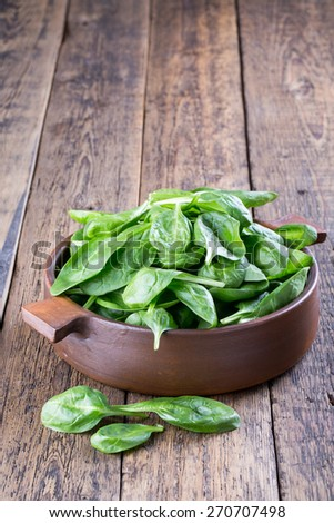 Fresh baby spinach leaves in a bowl on a wooden background - stock photo